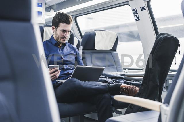 Businessman working in train using laptop - UUF12628 - Uwe Umstätter/Westend61