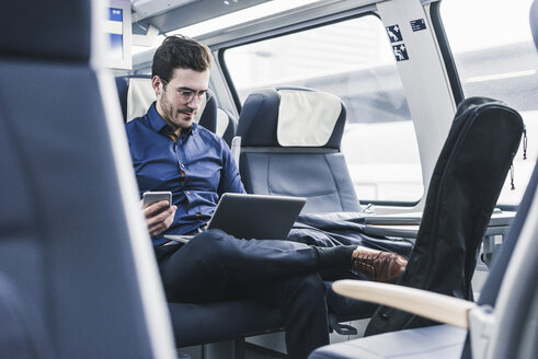 Businessman working in train using laptop - UUF12628