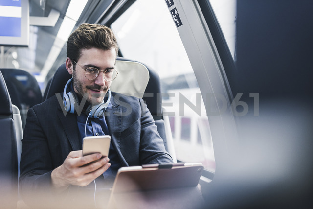 Businessman in train with cell phone, headphones and tablet - UUF12631 - Uwe Umstätter/Westend61