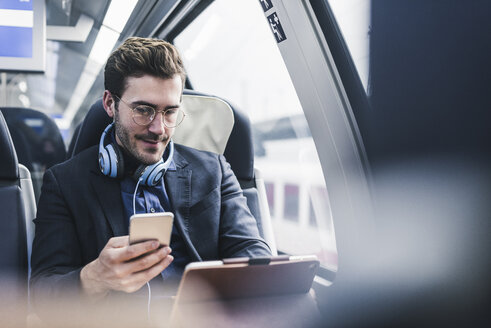 Businessman in train with cell phone, headphones and tablet - UUF12631