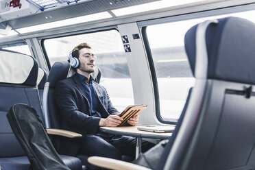 Businessman in train relaxing listening to music - UUF12634