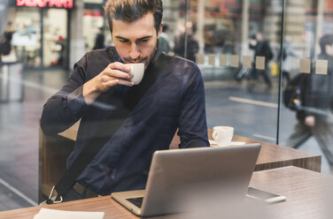 Young businessman in a cafe at train station with cup of coffee and laptop - UUF12640