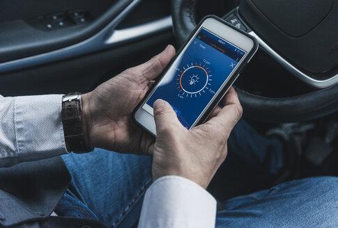 Man in car adjusting smart home device via smartphone - UUF12652
