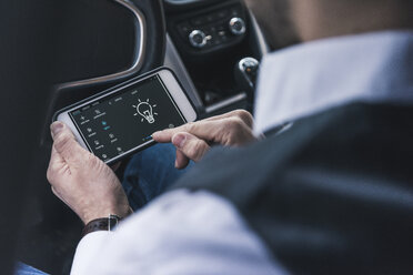 Man in car adjusting smart home device via smartphone - UUF12655