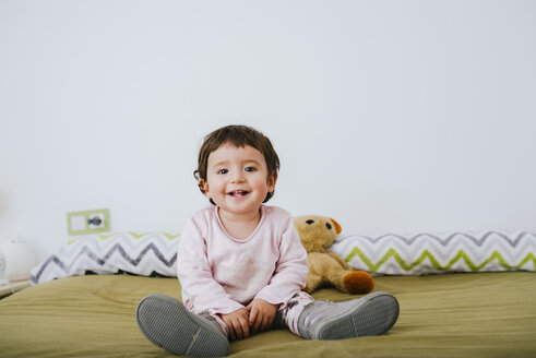 Portrait of happy baby girl sitting on bed - GEMF01871