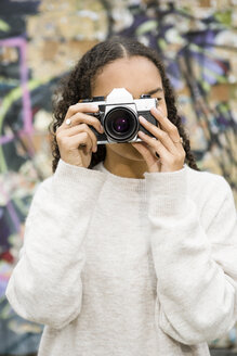 Germany, Berlin, young woman taking pictures with an old camera in front of graffiti - OJF00229