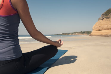 Close-up of young woman exercising yoga at a beach - ABAF02199