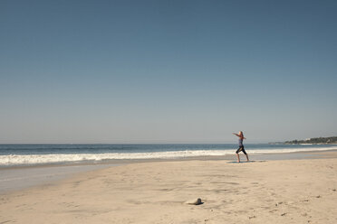 Young woman exercising yoga at a beach - ABAF02202