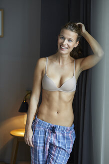Portrait of laughing young woman standing wearing bra and pyjama pants - PNEF00403