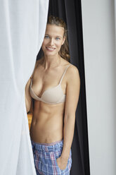 Portrait of smiling young woman standing wearing bra and pyjama pants - PNEF00406