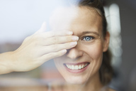 Portrait of laughing young woman behind windowpane covering her eye - PNEF00409