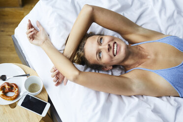 Portrait of laughing young woman lying in bed - PNEF00415