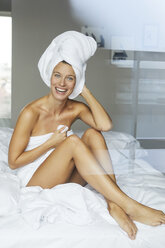 Portrait of happy young woman sitting on bed wrapped in towels - PNEF00418