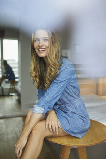 Smiling young woman sitting on table behind windowpane - PNEF00421