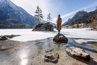 Germany, Bavaria, Ramsau, young woman standing on stone, Hintersee - WVF00921