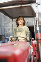 Portrait of confident woman driving a tractor - PESF00900