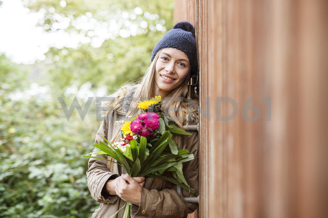 Portrait of smiling young woman holding bunch of flowers outdoors - PESF00903 - Peter Scholl/Westend61
