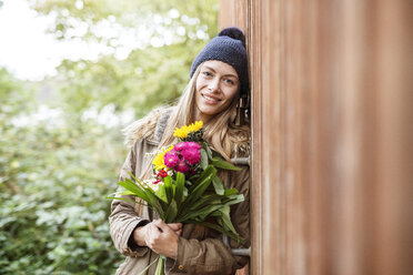 Portrait of smiling young woman holding bunch of flowers outdoors - PESF00903