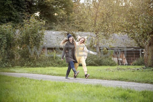 Two happy women walking in rural landscape - PESF00909 - Peter Scholl/Westend61