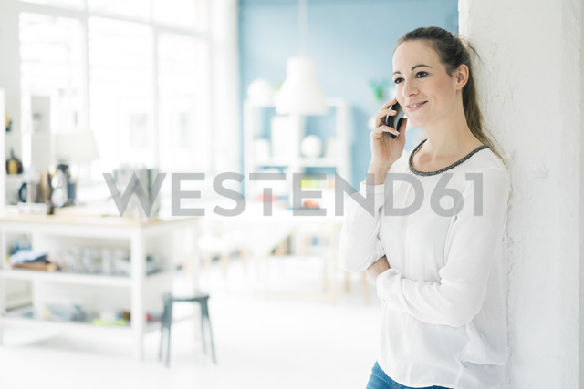 Portrait of smiling woman son the phone standing in a loft - MOEF00707