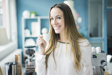 Portrait of happy businesswoman drinking espresso in kitchen of a loft - MOEF00716