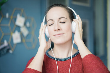 Portrait of woman with eyes closed  listening music with headphones - MOEF00722