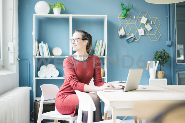 Smiling woman sitting at table with laptop looking out of window - MOEF00728