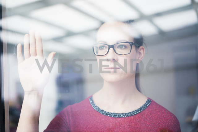 Portrait of pensive woman wearing glasses looking out of window - MOEF00731