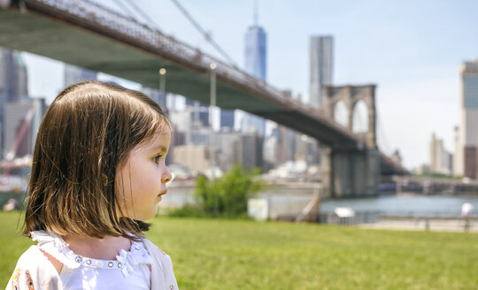 USA, New York, Brooklyn, Portrait of little girl in park looking aside with Brooklyn Bridge in background - DAPF00873