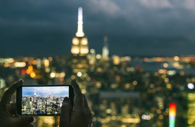 USA, woman hands holding smartphone while taking a photo of Manhattan at night - DAPF00885