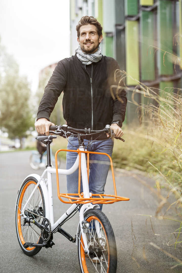 Smiling man with bicycle on a lane - PESF00918 - Peter Scholl/Westend61