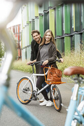 Portrait of smiling couple with bicycle on a lane - PESF00921