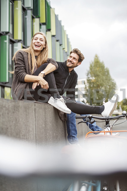 Happy couple with bicycles sitting on a wall - PESF00924