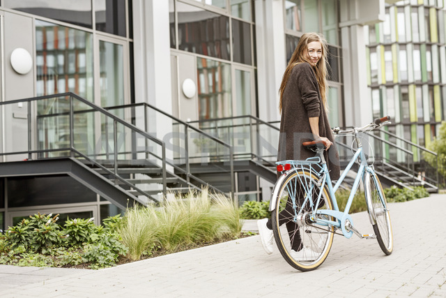 Portrait of smiling woman with bicycle in front of a building - PESF00936 - Peter Scholl/Westend61