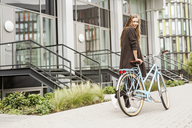 Portrait of smiling woman with bicycle in front of a building - PESF00936