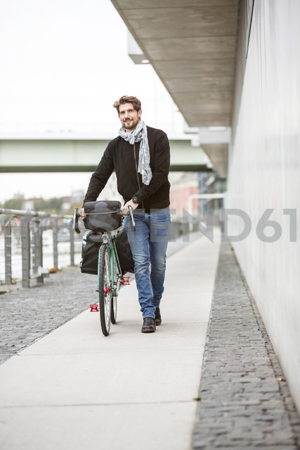 Smiling man pushing bicycle on a path - PESF00939 - Peter Scholl/Westend61