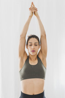 Woman practicing yoga raising her arms - ASCF00789