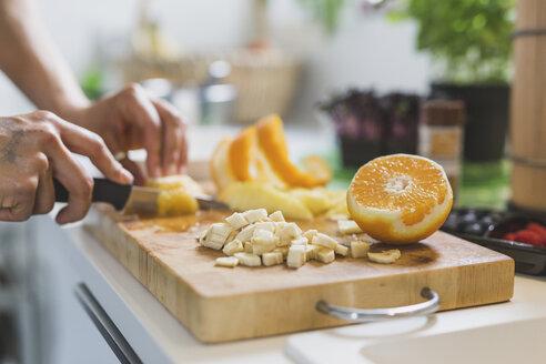 Woman preparing fruit on chopping board - ASCF00792