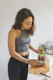 Woman preparing salad to go on chopping board - ASCF00801