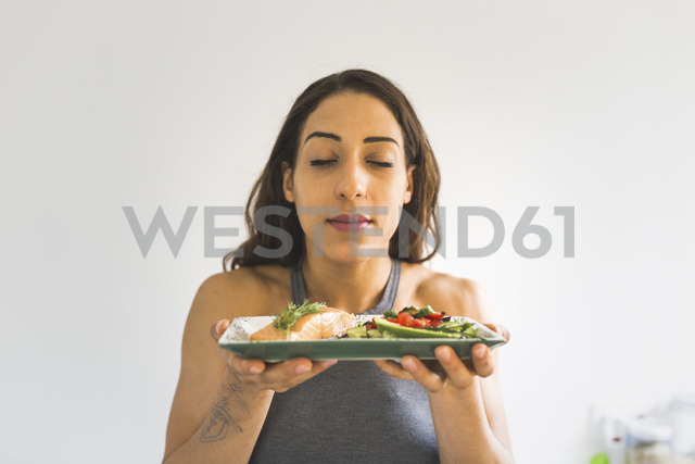 Woman holding plate with vegetables and salmon - ASCF00810