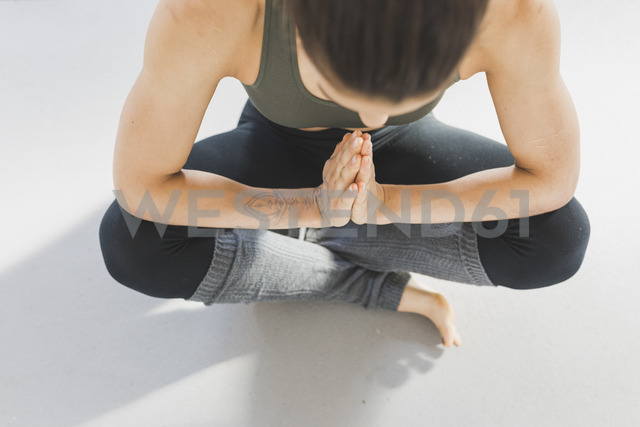 Overhead view of woman sitting on floor practicing yoga - ASCF00813