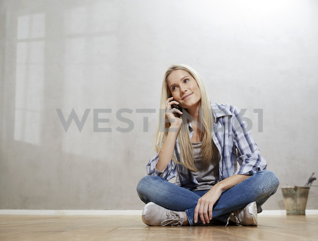 Portrait of smiling blond woman on the phone sitting on the floor in front of grey wall - FMKF04744 - Jo Kirchherr/Westend61
