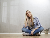 Portrait of smiling blond woman on the phone sitting on the floor in front of grey wall - FMKF04744