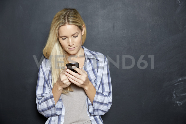 Blond woman standing in front of blackboard looking at cell phone - FMKF04747 - Jo Kirchherr/Westend61