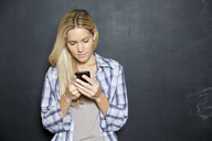 Blond woman standing in front of blackboard looking at cell phone - FMKF04747
