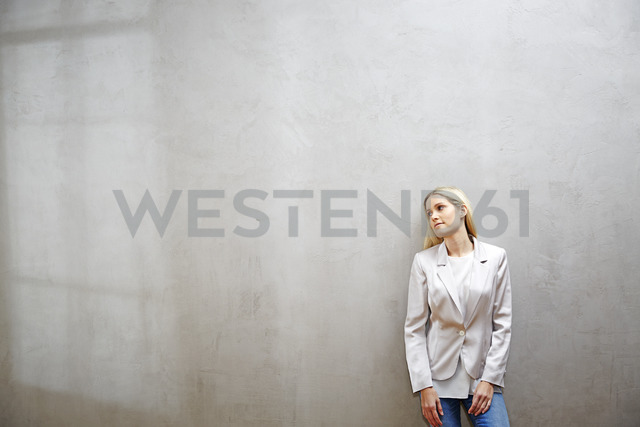 Relaxed businesswoman standing in front of grey wall - FMKF04750