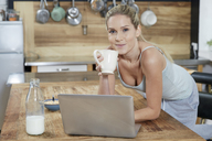 Portrait of smiling blond woman with laptop in the kitchen drinking coffee - FMKF04756