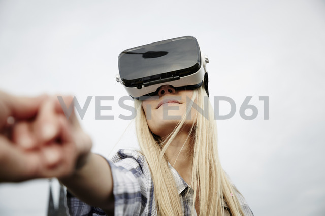 Woman wearing Virtual Reality Glasses holding hands - FMKF04762 - Jo Kirchherr/Westend61