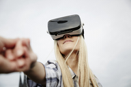 Woman wearing Virtual Reality Glasses holding hands - FMKF04762