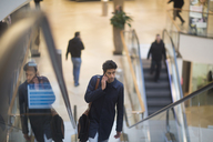 Man on the phone standing on escalator in a shopping mall - SGF02163